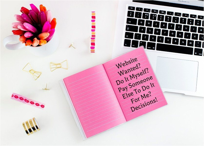 laptop on desk with pink notepad